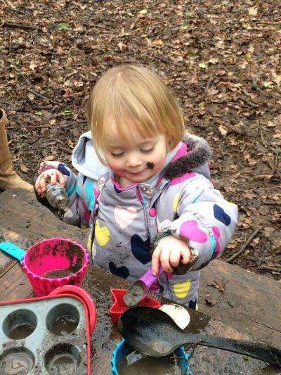 Toddler with muddy face standing in front of muddy table using a spoon to fill a cake case with mud