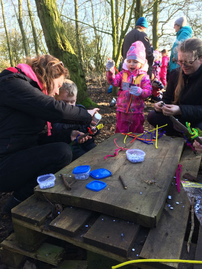 Toddlers with mothers making things using pipe cleaners on a wooden board in woodland