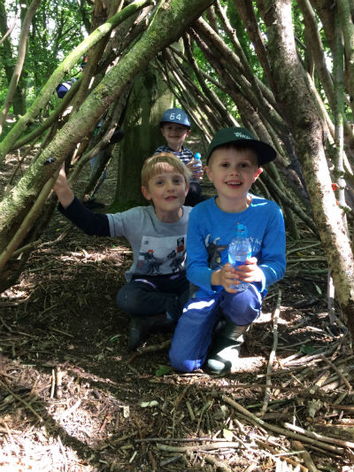 3 boys sitting in a woodland den made from sticks