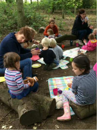 Children and adults sitting on logs or checked picnic rugs in woodland