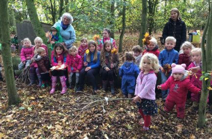 Group of 17 children and 2 adults sitting on and standing near a log in woodland holding leaves and sticks