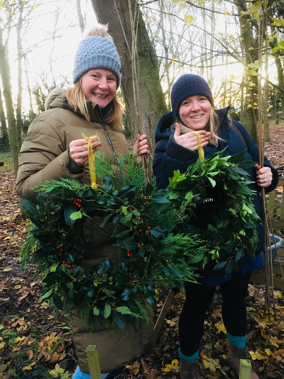Two women holding Christmas wreath